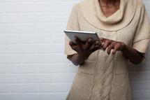 African-American woman looking at an iPad screen