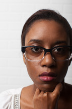 stoic face of an African-American woman with reading glasses