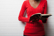 torso of an African-American woman reading a Bible