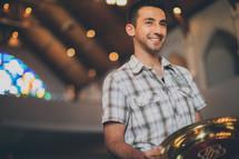 Smiling man holding a brass platter.