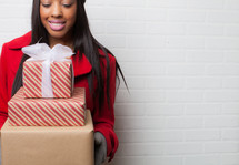 an African-American woman holding wrapped Christmas gifts