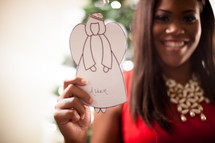 A young African-American woman holding a paper angel