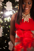 An African-American woman standing in front of a Christmas tree holding a wrapped gift