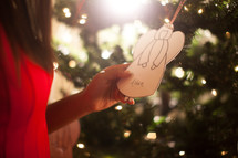 An African American woman holding an Angel Christmas ornament