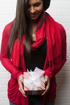 An African-American woman holding a Christmas gift with her head bowed in prayer