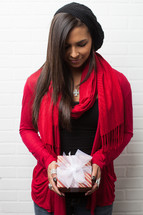 An African-American woman holding a wrapped Christmas gift with her head bowed in prayer