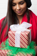 an African-American woman with head bowed holding Christmas gifts
