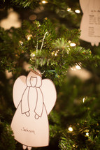 an angel ornament hanging on a Christmas tree