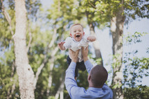 man lifting his toddler son in the air