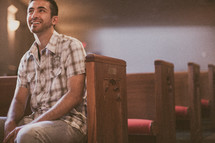 man sitting in a church pew smiling