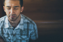man sitting in a church pew praying to God