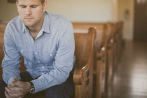 man sitting in a pew in a church in prayer