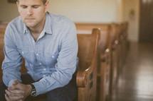 man sitting in a pew in a church in prayer