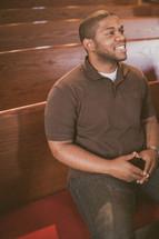 man sitting in a church pew smiling