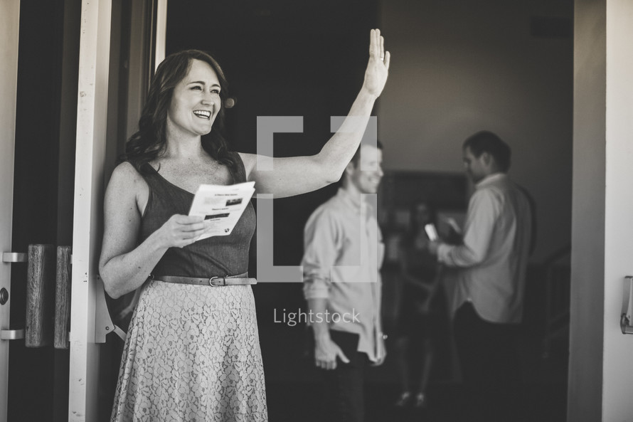 Woman standing in a doorway, program in hand, waving and smiling.