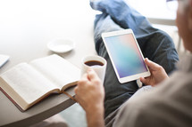 man looking at an iPad screen and an open Bible