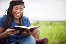 joyful African-Ameican woman reading a Bible outdoors