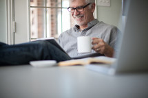 man looking at an iPad screen and drinking coffee