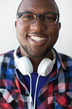 face of a man wearing reading glasses and headphones around his neck with a beard