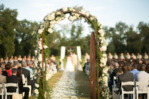 an arch an alise at a wedding ceremony