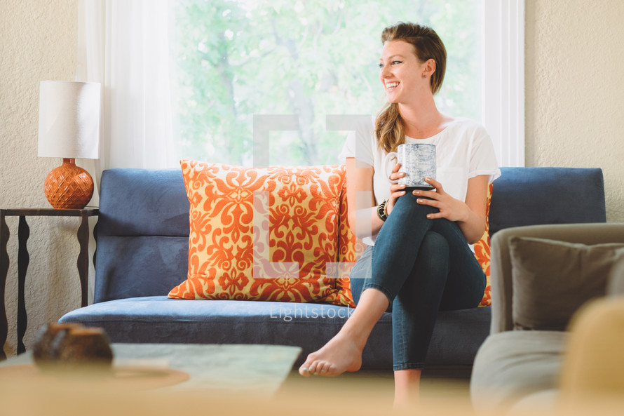 woman sitting on a couch in her living room holding a coffee mug