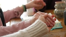 holding hands in prayer at a women's group Bible study sitting around a table