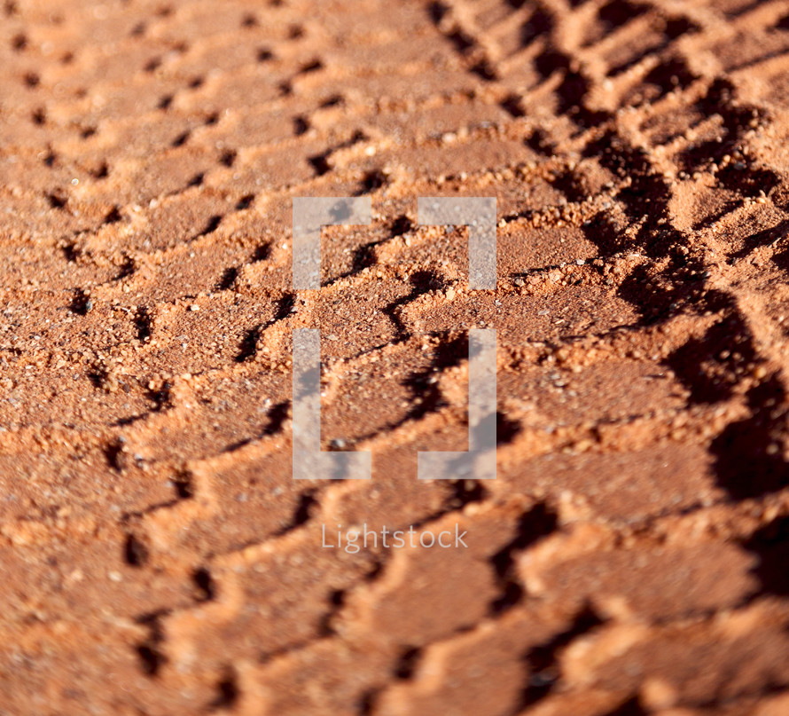 tire tracks in red sand