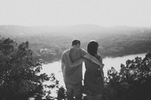 couple holding each other enjoying a view of a river