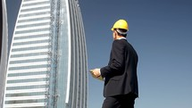 engineer in a hardhat in front of a high-rise building