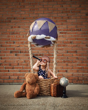 a little girl in a hot air balloon and telescope