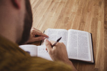 man reading a Bible and writing a journal