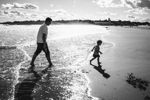 Father and son playing by water at the beach.