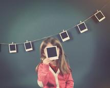 a child holding a polaroid photograph