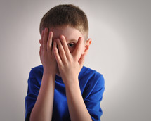 a boy covering his face and peeking through his fingers