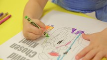 toddler boy coloring a coloring page with crayons at Sunday School