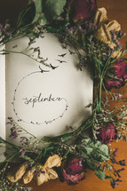 the word September and a wreath of flowers