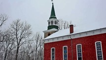 red church with steeple in the falling snow