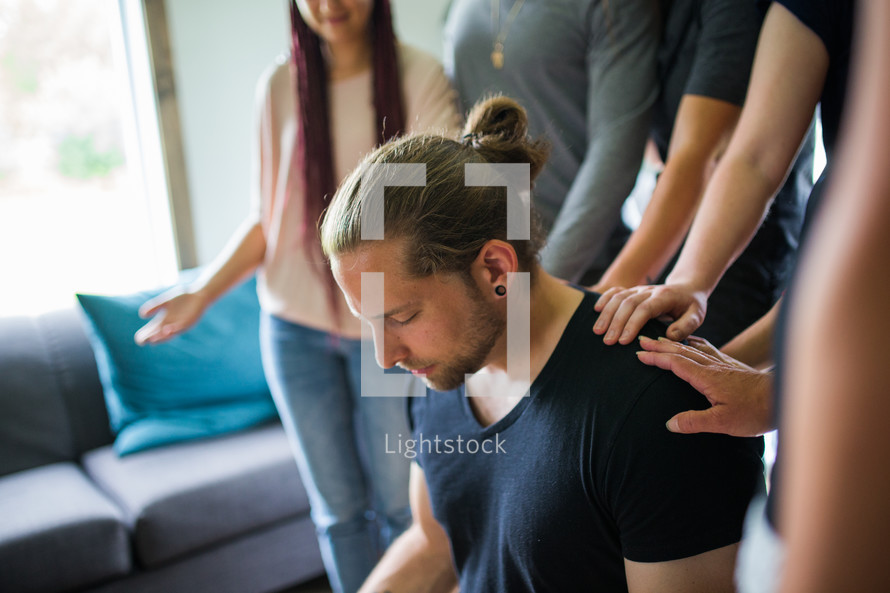 group lying hands on a man praying over him