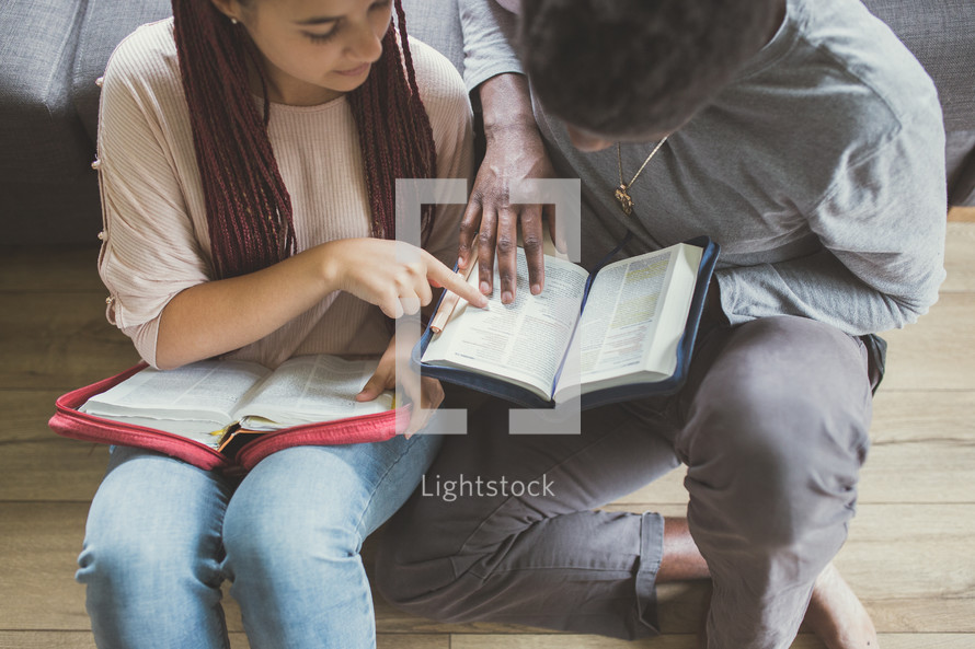 a couple sitting on the floor reading Bibles together