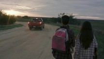 migrant family walking on a dirt road