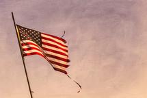 a torn flag on a flag pole