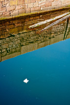 stone wall and reflection on water