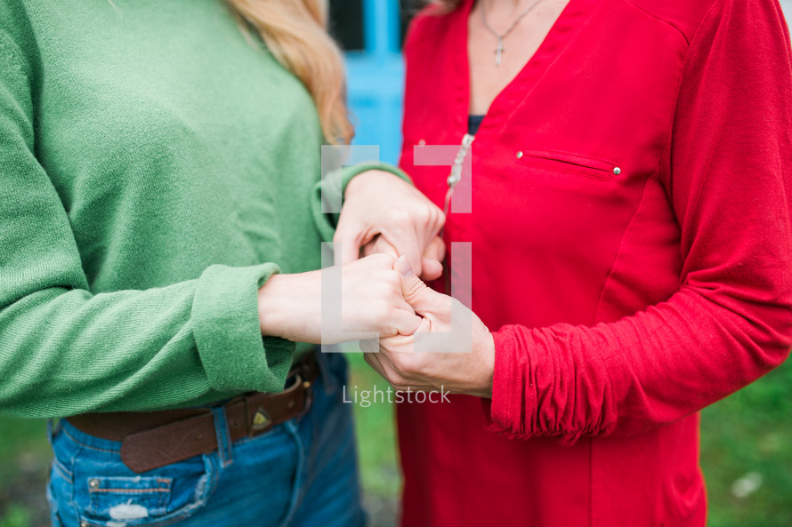mother and daughter holding hands in prayer
