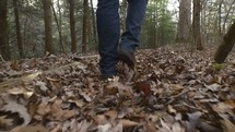 man walking through fall leaves in a forest