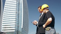 engineer and businessman in discussion in front of a high-rise building