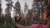 Young girl shooting a slingshot in the forest. - 2 of 2