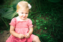 Toddler girl in pink dress with flower in hair sitting in garden.