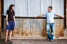 man and woman leaning against a ware house wall talking