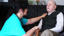 Senior man talking with nurse at home