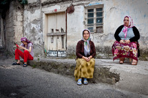 women wearing scarves on their heads sitting on a street curb